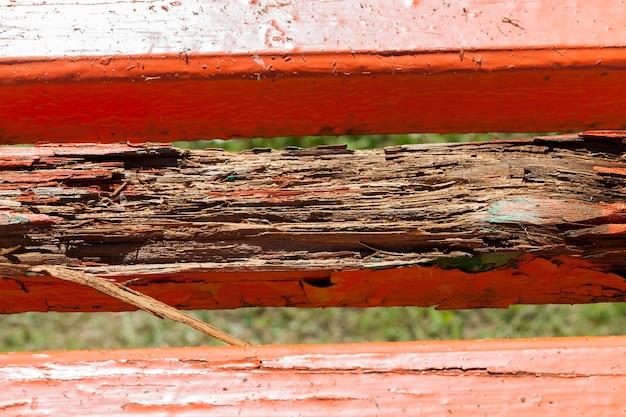보드의 썩은 부분이있는 오래된 벤치는 빨간색으로 칠해져 있습니다.