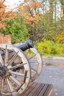 戦場の古い真ちゅう製の大砲。2つの木製の支柱の上に立っている古い金属製の大砲
