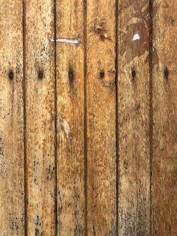 ヴィンテージの背景に釘が入った古い茶色の木の背景。