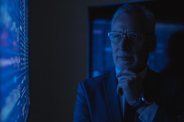 闇の実験室のブルースクリーンの近くに立っている老人実業家