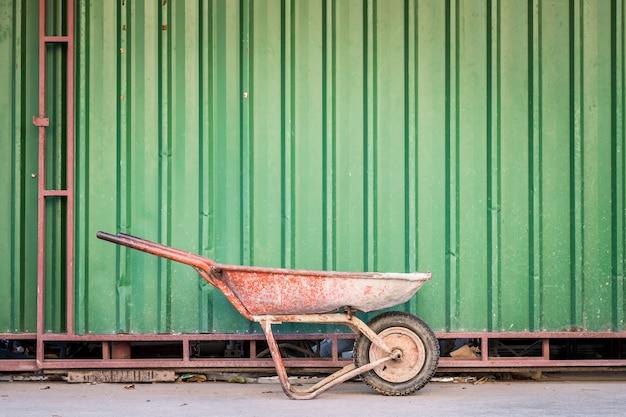緑の壁と古いセメントカート。
