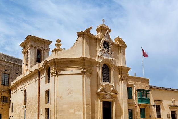 Старая церковь в стиле барокко на фоне голубого неба. фасад украшен колоннами и арками.
