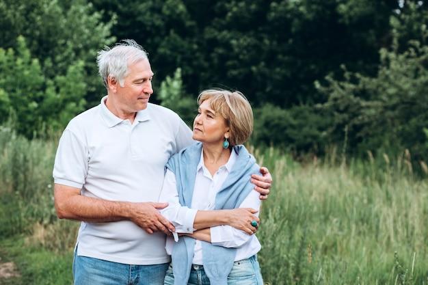 老夫婦は自然の中を歩き、手をつないで寄り添う