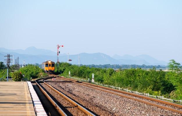 タイの北東線にある田舎の駅のホームに、コピースペースのある正面図で、ローカル列車の古い気動車が到着しています。