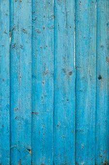 古いフェンスは緑色の断片で、塗料は木製の表面から剥がれます