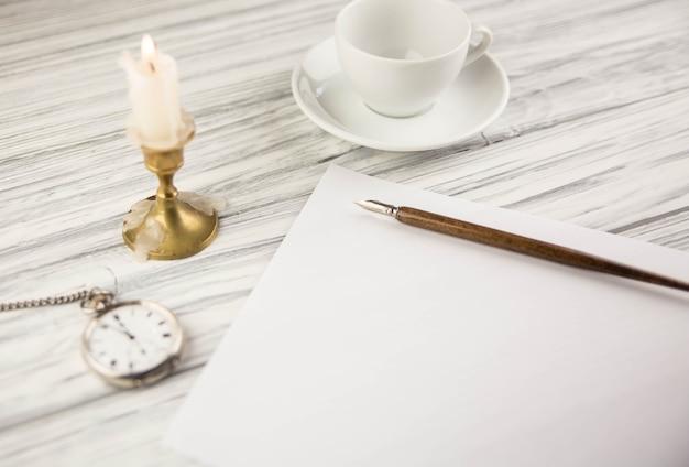 Старая ручка перо и лист бумаги со свечой