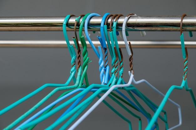Старая группа вешалок располагается на штанге из нержавеющей стали бельевой веревки, летом у стены дома, вид спереди на место для копирования.