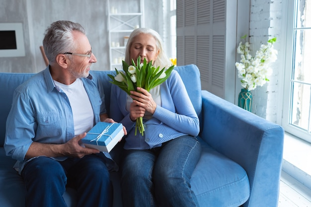 Старик дарит подарок и цветы женщине