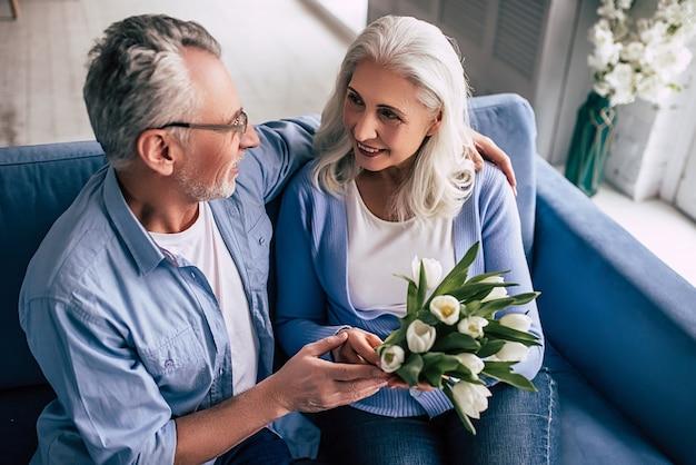 Старик дарит цветы пожилой женщине