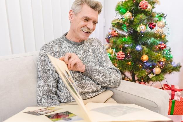 노인은 크리스마스 트리 근처에서 사진 앨범을 들고 있다