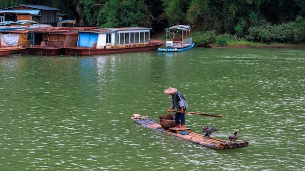 Старик на плоту пересекает реку ли, известную также как реку лицзян.