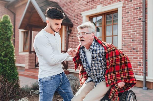車いすの老人と息子が庭を歩いている年配の父親が車いすに乗るのを手伝っている男