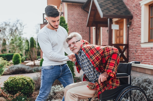 車いすの老人と息子が庭を歩いていて、年配の父親を助けている男性