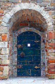 Старая металлическая дверь с каменной кладкой с замком