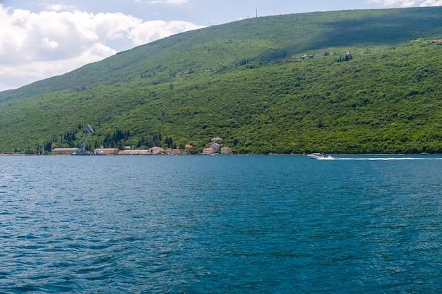 古い軍用クレーンが小さな港モンテネグロボカコトル湾で貨物を降ろす