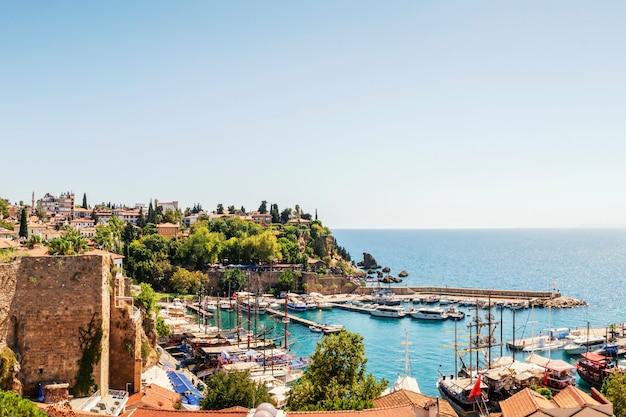 Старый порт калеичи в анталии и крепость. яхты в гавани залива, синего моря и неба. туристическое историческое место в анталии, турция.