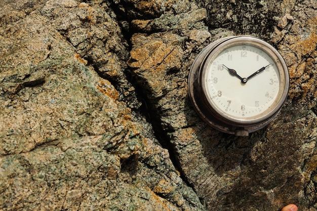 Старые круглые корабельные часы на скале летом на скалистом берегу моря