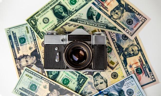 오래 된 망가진 아날로그 카메라는 미국 달러 현금 지폐에 있습니다. 돈. 카메라. 사진술