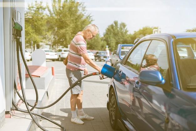 Пожилой пожилой мужчина заправляет свою машину бензином на заправочной станции турист, путешествующий
