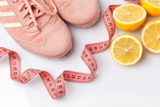 古いスニーカー、メーターテープ、白地にレモン。フィットネスと健康的なライフスタイルの概念