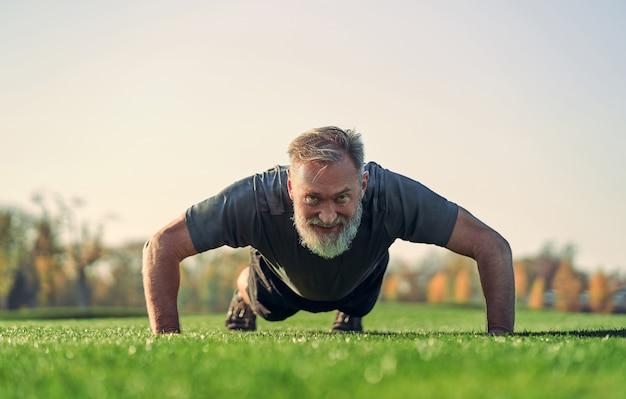 잔디를 밀고 있는 늙은 스포츠맨