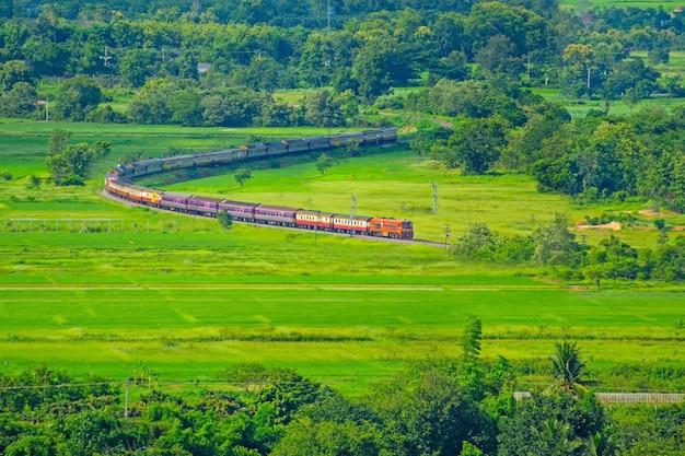 Старый тайский поезд курсирует между бангкоком и чиангмаем. таиланд проходит мимо рисового поля.