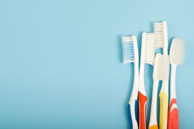 使用されていた古い歯ブラシは、青色の背景に期限切れの(破損した)さまざまな色を使用していました。コンセプト医療業界のプロの歯科医の製造に使用されるか、歯ブラシを交換する必要があります。