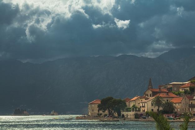 人気のある観光旅行先に海岸線の暗い雲があるモンテネグロの旧市街