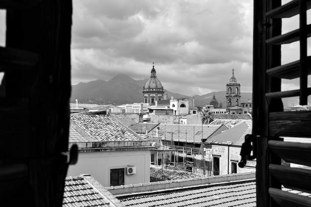 셔터가 있는 열린 창문을 통해 팔레르모의 구시가지, 시칠리아, 이탈리아
