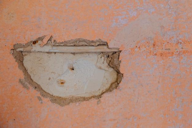Старая стена рушится, видна кирпичная стена и текстурированный кусок электрического кабеля.