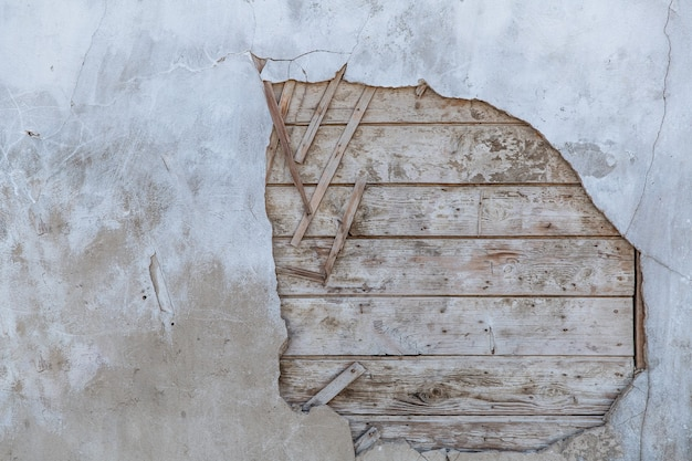 崩れかけている古い壁。あなたは家が建てられている木の板を見ることができます。
