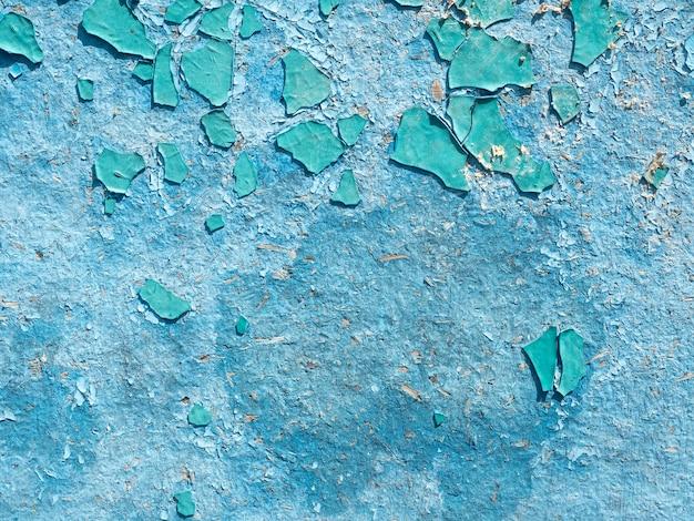 Старая обветренная отслаивающаяся краска на стене синего цвета. крупный план, фон, текстура