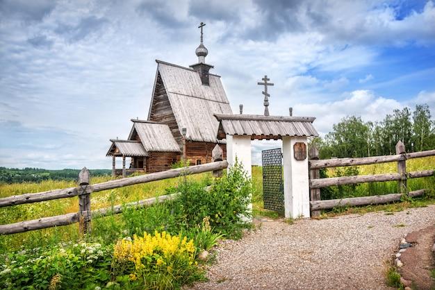 Старая деревянная церковь воскресения христова на горе левитан в плесе и желтые цветы у ворот в солнечный летний день. надпись: церковь воскресения христова.