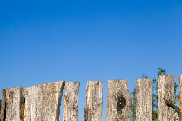 Старый деревянный забор из обрезков деревьев и старых досок, крупный план конструкции, охраняющей необходимую территорию.