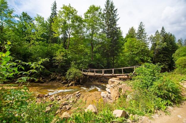 山の森の小さな川に架かる古い木製の弱い橋。