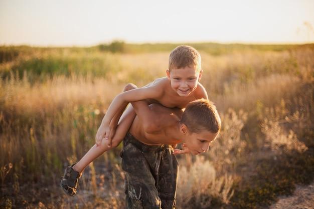 Старший брат несет своего смеющегося младшего брата на спине в летнем поле на закате