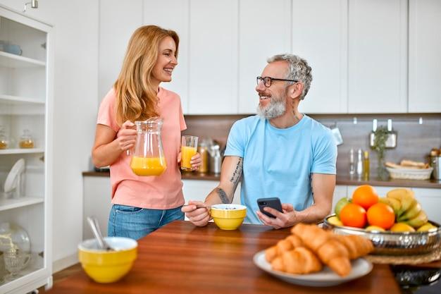 노부부는 아침을 먹고 즐거운 시간을 보냅니다. 성숙한 남자가 시리얼을 먹고 부엌에서 전화를 사용합니다.