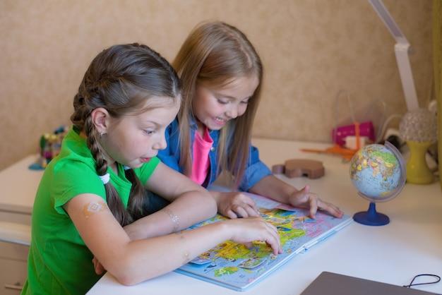 姉は、書面による授業と学校の準備で、幼い子供たちを助けます