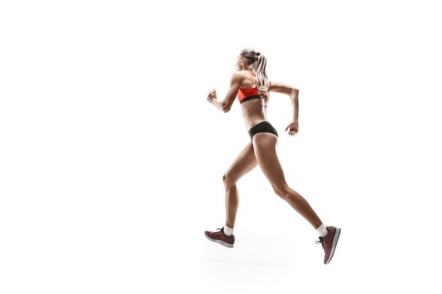 白いスタジオの背景に走ってジャンプするランナーの1つの白人女性のシルエット