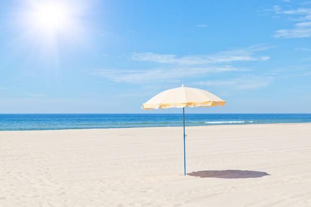 Единственный пляжный зонт на море летом под солнцем.
