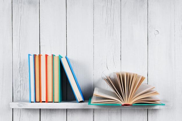 開いた本と他のマルチカラーの本。木製の棚に。木製の白いテーブル。