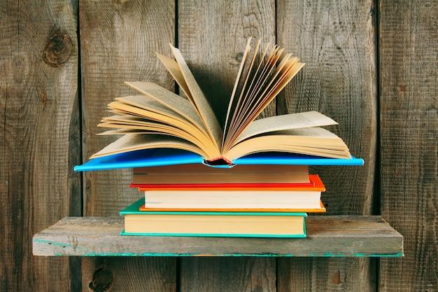 책 더미에 펼친 책. 나무 선반에.