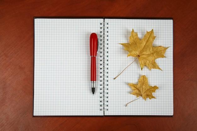 Открытый блокнот и красная ручка с осенним листом на деревянном столе