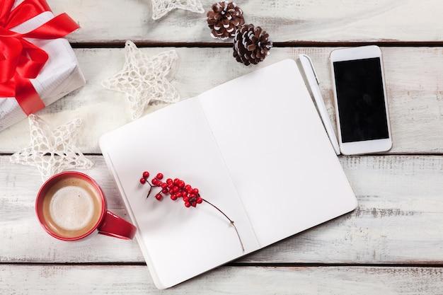 Открытый блокнот на деревянном столе с телефоном и рождественскими украшениями.