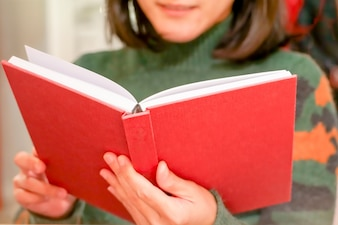 The open red book is holding/reading on women hand at home