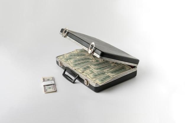 現金ドルのお金でいっぱいの開かれたヴィンテージケース、色の表面に百紙幣