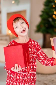 Открытие ребенок присутствует на елке дома мальчик в красной пижаме с подарками.
