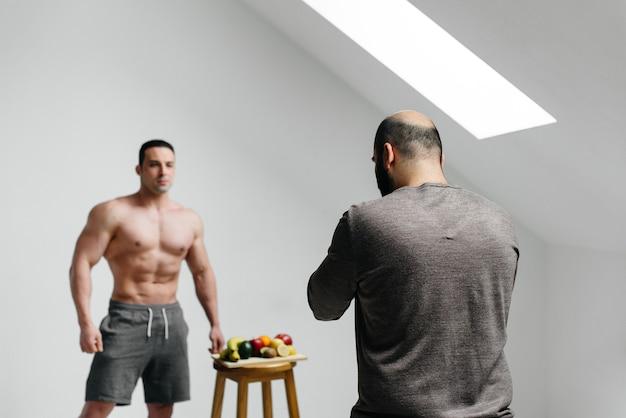 Оператор ведет блог со спортсменом на тему тренировок и здорового образа жизни. блогер. кинотеатр.