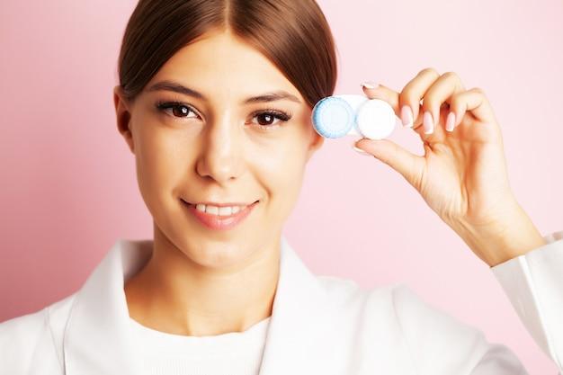 Офтальмолог держит контейнер с контактными линзами возле глаз