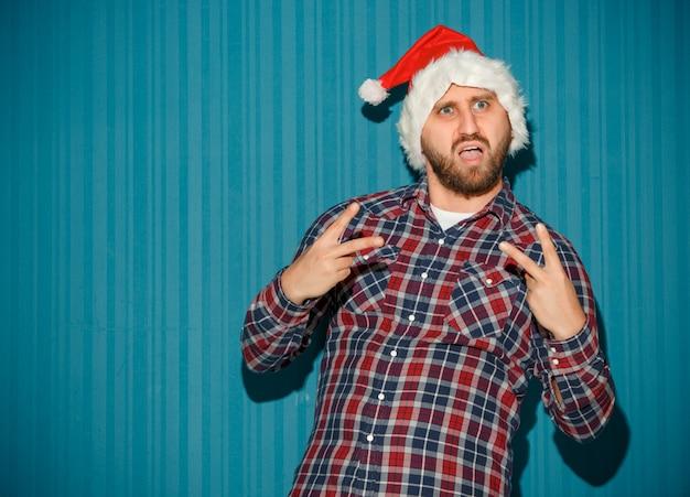サンタの帽子をかぶっている独断的なクリスマスの男